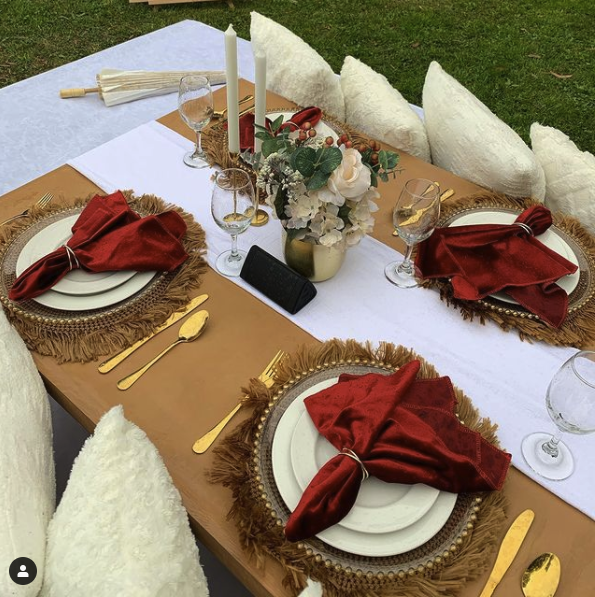 luxury picnic with cream pillows and fancy tablewear